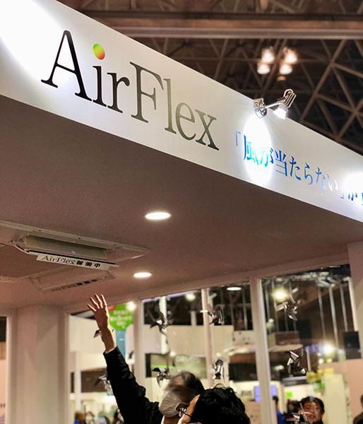 AirFlexの吹出し口に手を伸ばして風を確認するお客様